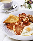 English breakfast: fried egg, bacon, tomato and sausage