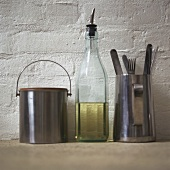 Kitchen shelf with small bucket, oil bottle and cutlery