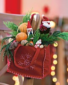 Red felt bag filled with Father Christmases, mandarins and nuts