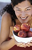 Young woman holding bowl of nectarines
