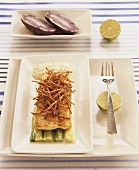 Grouper fillet with straw potatoes on spring onion