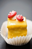 Petit four with yellow glacé icing and fly agarics