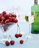 Bowl of cherries and two glasses of white wine