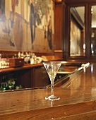 A glass of Martini with olive in a bar