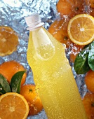 A bottle of orangeade and oranges