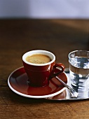 A cup of espresso and a glass of water