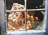 Hexenhaus aus Honigkuchen hinter einem verschneiten Fenster