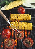 Corncobs and tomatoes with herbs on the barbecue