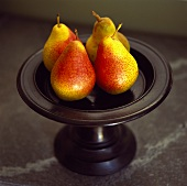 Four pears on a pedestal stand