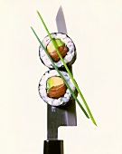 Two maki sushi with salmon and avocado on knife