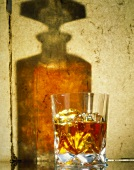 A glass of whisky, shadow of a whisky bottle behind it