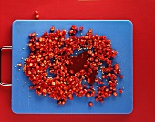 Chopped chili peppers and chili sauce on blue board