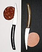 Two knives, each with a slice of sausage