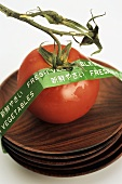 Tomato on wooden bowls with 'Fresh Vegetables' sticker