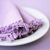 Weisser Teller mit lila Stoffservietten