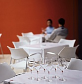 Tables and chairs in dining room, couple in background