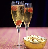 Two glasses of champagne with raspberries & bowl of almonds