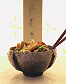 Tofu slices with vegetables and sesame in small bowl