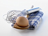 A brown egg on wooden spoon with egg whisk & kitchen cloth