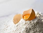 Egg, broken open, lying on flour