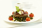 Beef fillet on green asparagus with cherry tomatoes