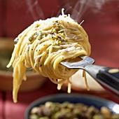 Dampfende Linguine mit Pesto um eine Gabel gewickelt