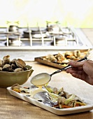 Pouring sauce over sea bass and mussels