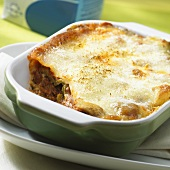 Lasagne, with a piece taken, in a baking dish