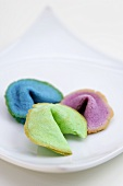 Three different coloured fortune cookies on plate