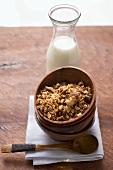 Muesli in wooden bowl, milk behind