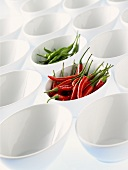 Lots of white bowls, two full of chili peppers