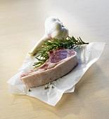 A lamb cutlet, rosemary and garlic bulb