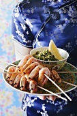 Serving shrimp kebabs with dip on a plate