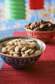 Small bowl of almonds, party decorations behind
