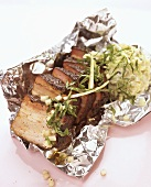 Roast pork with salad on aluminium foil