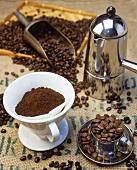 Stillleben mit Kaffeebohnen, Kaffeepulver und Kaffeekanne
