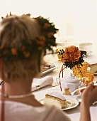 Bride with wreath of flowers in her hair eating cake