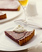 A piece of chocolate tart with cream