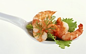 Shrimp tail, lettuce leaf and dill on spoon