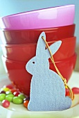 Blue felt bunny in front of red bowls