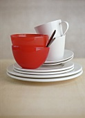 White plates, white coffee cups and red bowls