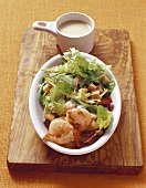 Salad leaves with shrimps, croutons and salad dressing