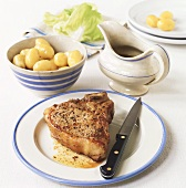 Pork chop with potatoes and lettuce