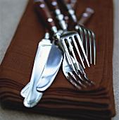 Knives and forks on brown napkins