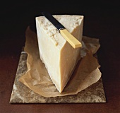 A piece of Parmesan cheese with knife