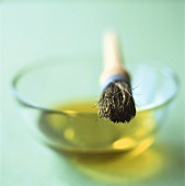Small bowl of olive oil with brush