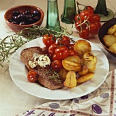 Lamb steak with olive butter, roast potatoes & cherry tomatoes