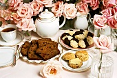 Fruit loaf, scones, cookies and tea on table with roses