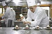 Female chef piping cream onto desserts