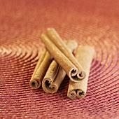 Four cinnamon sticks on red background